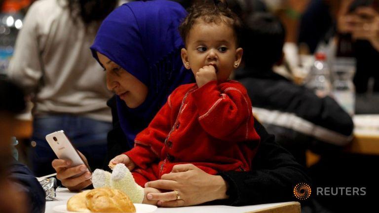 Velkledd flyktning med smarttelefon og gullring. Ungen hennes har ørepynt og fine fløyelsklær.